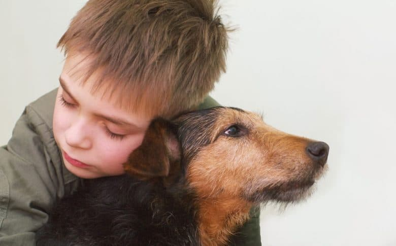 A child hugging his dog