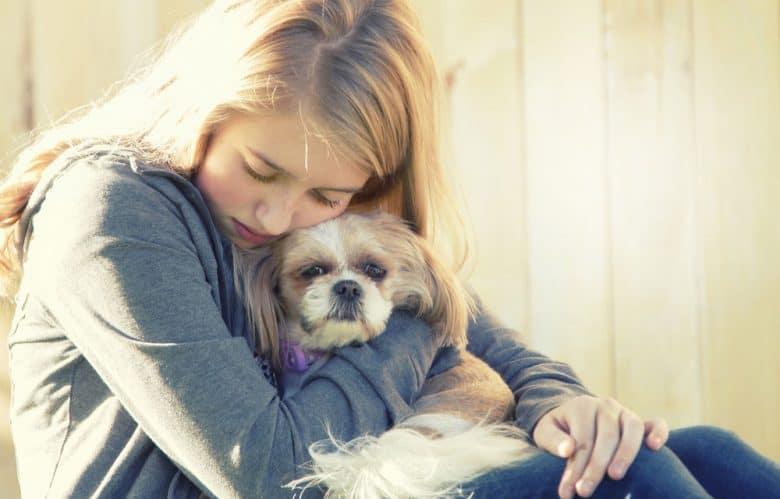 A teenage girl hugging tight her dog
