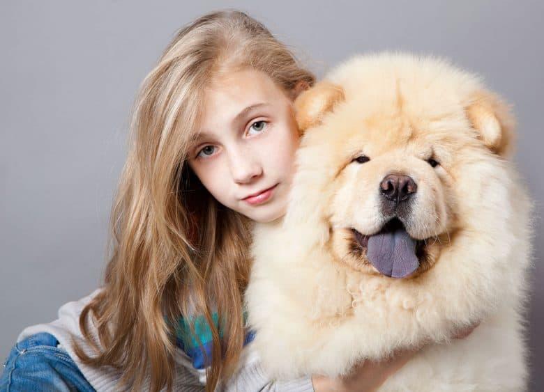 Teen girl hugging Chow Chow dog