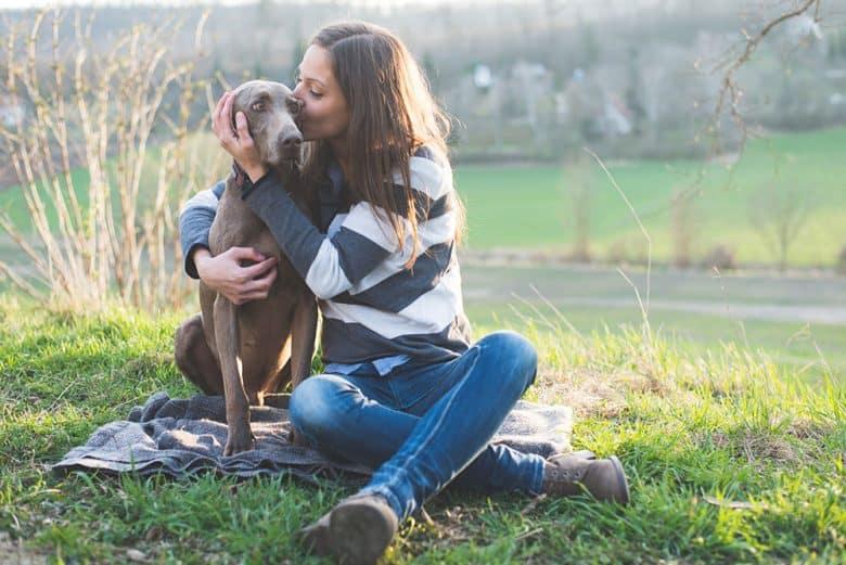 Woman kissing her Weimaraner dog