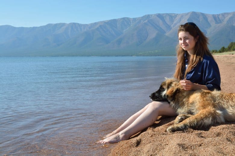 A Leonberger resting with a woman on a lake