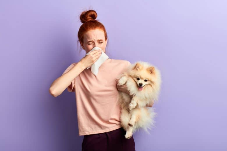 a sick red hair woman holding a Pomeranian dog