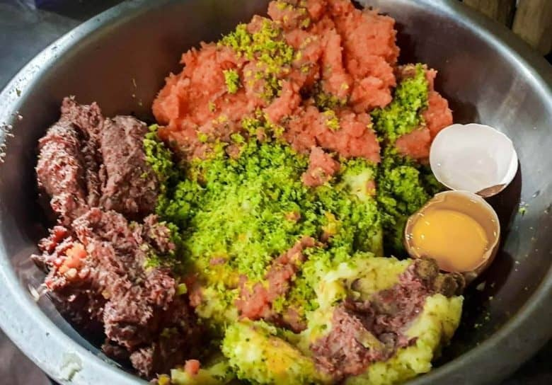 Ground meats with vegetables and raw egg on a metal bowl