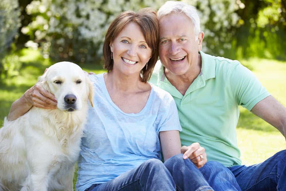 happy senior couple sitting with their Labrador Retriever